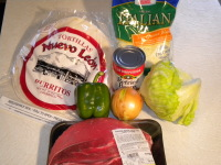 This is a picture of the ingredients that will be used for the recipe to make authentic Mexican Burritos including meat, cheese, beans, onion, lettuce, green pepper, and special burrito tortillas.