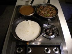 Here is the Mexican Burrito recipe being prepared on the stove, with a frying pan full of the meat and onion mixture, a frying pan of refried beans, and a special burrito tortilla being heated.