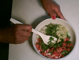 Here some of the ingredients of the Mexican Ceviche recipe being mixed in a bowl including tomatoes, onion, cilantro, and avacado.