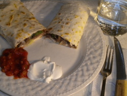 This is a picture of the finished burrito made from this recipe, served complete with condiments sour cream and mexican salsa, and a soft drink.